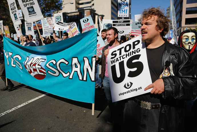 """Demonstarators carry signs at the """"Stop Watching Us: A Rally Against Mass Surveillance"""" march near the U.S. Capitol in Washington, October 26, 2013. (Reuters / Jonathan Ernst)"""