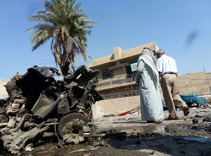 Iraqis look at the remains of a vehicle following an explosion at a small bus station on October 27, 2013, in the the Mashtal district of the capital Baghdad (AFP Photo / Sabah Arar)