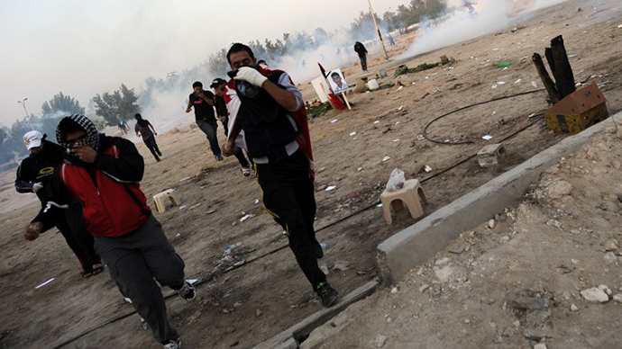 Bahraini anti-government protesters run for cover from tear gas during clashes with riot police in the Shiite village of Abu Saiba, west of Manama, on December 20, 2011 that began following a memorial service for Shiite youth Ahmed Radi al-Qassab (AFP Photo)