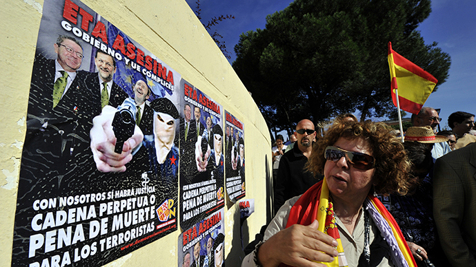 A woman looks at posters against ETA and the Spanish government during a gathering with thousands of Spaniards at Plaza de Colon on October 27, 2013. (AFP Photo / Gerard Julien)