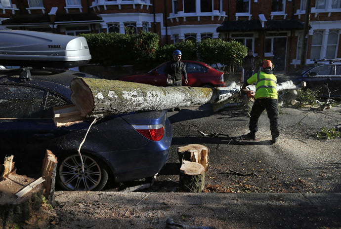 Workers clear a fallen tree from a street in south London October 28, 2013. (Reuters/Andrew Winning)