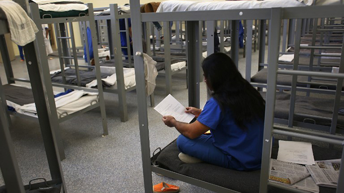 An immigration detainee from Bangladesh reads through his case papers while on his bunk at the Immigration and Customs Enforcement (ICE), detention facility (AFP Photo / John Moore)