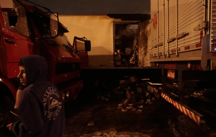 Riot sence of burnt trucks at highway in Sao Paulo, on October 28, 2013, following disturbances triggered by the accidental fatal shooting --on the eve-- of a 17-year-old boy by the police (AFP Photo / Miguel Schincariol)