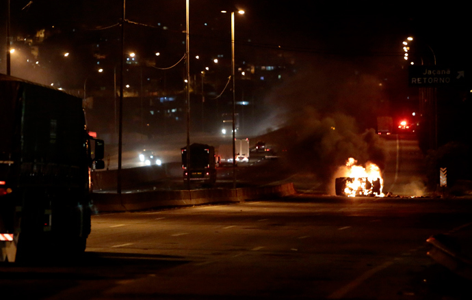 View of a car on fire in a highway in Sao Paulo, on October 28, 2013, following disturbances triggered by the accidental fatal shooting --on the eve-- of a 17-year-old boy by the police (AFP Photo / Miguel Schincariol)