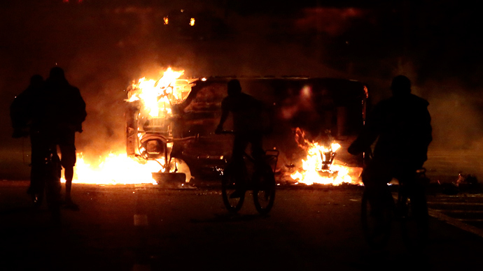 People ride bikes by a car on fire in a highway in Sao Paulo, on October 28, 2013, following disturbances triggered by the accidental fatal shooting --on the eve-- by police of a 17-year-old boy  (AFP Photo / Miguel Schincariol)
