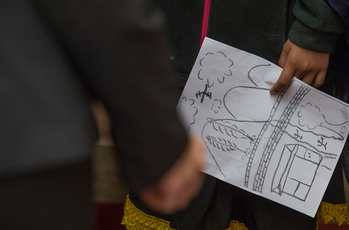 Nabila Rehman, 9, who was injured by a US drone strike in Pakistan, holds a hand drawn picture of the strike during a press conference on Capitol Hill in Washington, DC, October 29, 2013 (AFP Photo / Jim Watson
