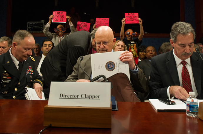 "Protesters with the organization Code Pink hold up placards as Director of National Security Agency (NSA) and Commander of US Cyber Command General Keith Alexander (L), Director of National Intelligence James Clapper (C) and Deputy Attorney General James Cole (R) arrive to testify before the House (Select) Intelligence Committee on ""Potential Changes to the Foreign Intelligence Surveillance Act (FISA)"" on Capitol Hill in Washington, DC, October 29, 2013 (AFP Photo / Jim Watson)"