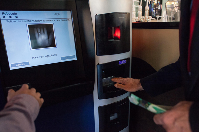 A user is instructed on how to scan his palm using scanning identification to ensure that a single user cannot exchange more than $1,000 in a single day day on the world's first bitcoin ATM at Waves Coffee House on October 29, 2013 in Vancouver, British Columbia (AFP Photo / David Ryder)