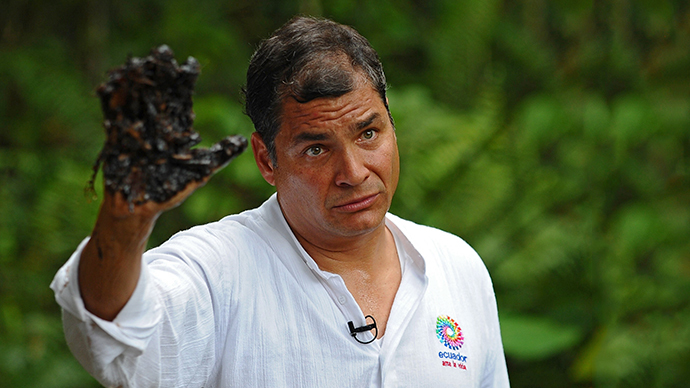 Ecuadorean President Rafael Correa shows his oil-covered hand at Aguarico 4 oil well in Aguarico, Ecuador (AFP Photo / Rodrigo Buendia)