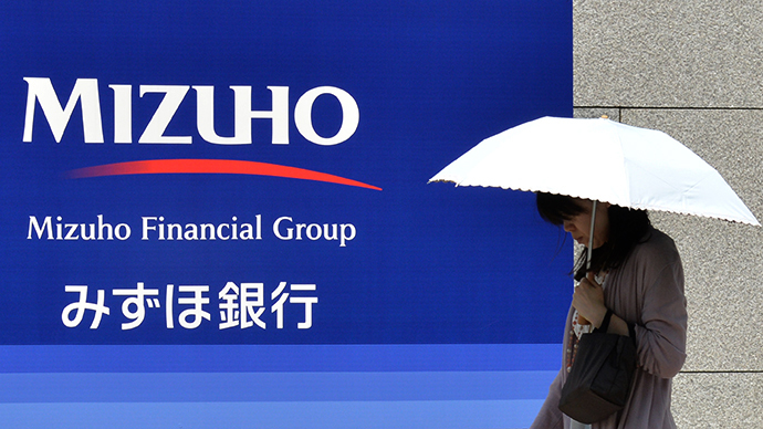 A woman walks in front of a signboard of Japan's Mizuho Financial Group in Tokyo (AFP Photo / Kazuhiro Nogi)