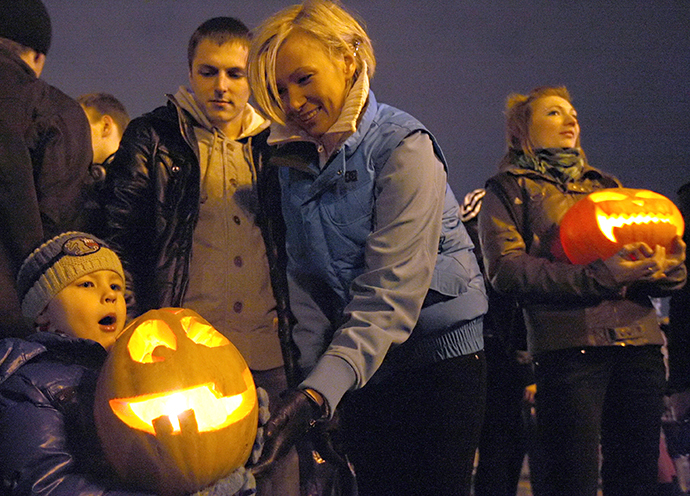 A kid holds a pumpkin during a flashmob marking Halloween celebrations at St. Petersburg's Palace Square. (RIA Novosti / Olga Maltseva)