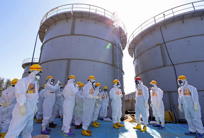 Japan's Prime Minister Shinzo Abe (in red helmet), wearing protective suit and mask, is briefed about tanks containing radioactive water by Fukushima Daiichi nuclear power plant chief Akira Ono (4th R) during his inspection tour to the Tokyo Electric Power Co. (TEPCO)'s tsunami-crippled Fukushima Daiichi nuclear power plant in Okuma, Fukushima Prefecture, September 19, 2013. (Reutes/Japan out)