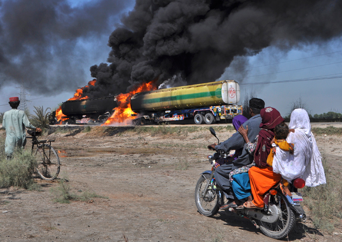 Residents on a motorbike look at burning fuel trucks attacked by gunmen on a highway near Shikarpur in Pakistan's Sindh province (Reuters / Nadeem Soomro)
