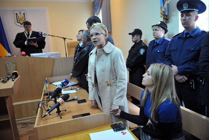 Yevgenia Carr (R) holds hands with her mother Yulia Tymoshenko who addresses Ukrainians while Rodion Kireyev, judge of Kiev Pechersky court reads a verdict to her during the sittings in Kiev on October 11, 2011. (AFP Photo / Sergei Supinsky)