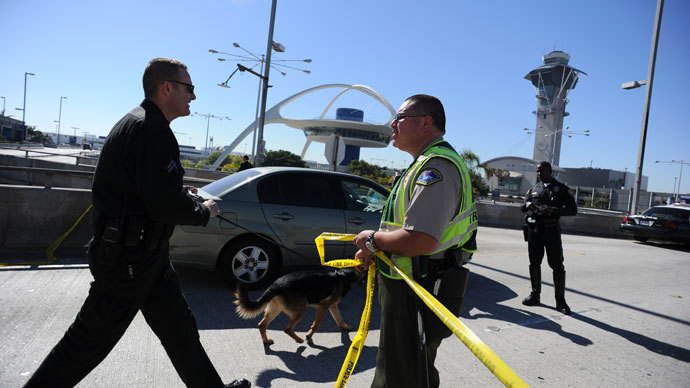A K-9 officer (L) crosses a crime tape line on November 1, 2013 after a gunman reportedly opened fire at a security checkpointin Los Angeles International Airport. (AFP Photo / Robyn Beck)