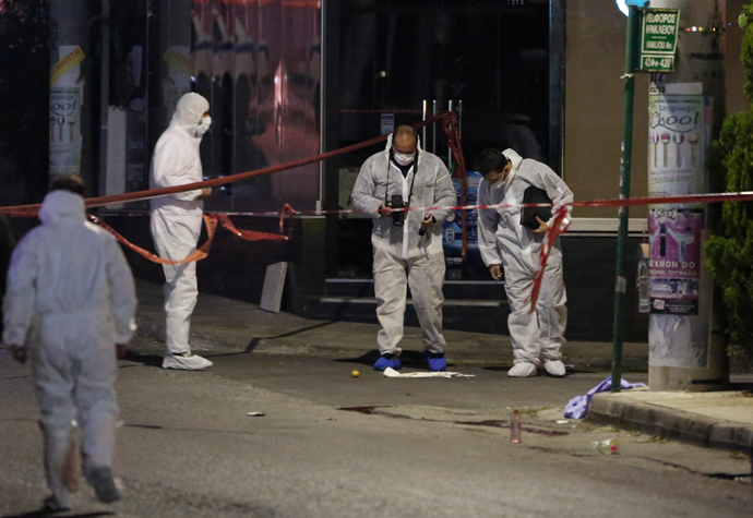 Police forensic experts search for evidence outside the local offices of far-right Golden Dawn party, following a shooting, in a northern suburb of Athens November 1, 2013 (Reuters / John Kolesidis)