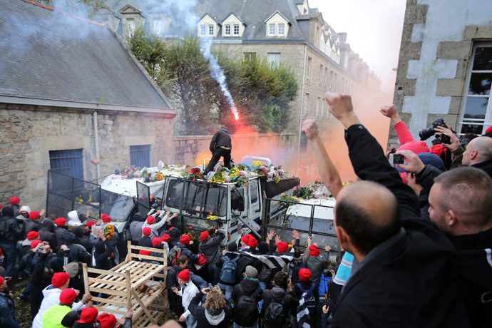 Protesters wearing red caps, the symbol of protest in Brittany, throw objects at a barricade held by French riot police during a demonstration to maintain jobs in Quimper, western France, November 2, 2013 (Reuters / Stephane Mahe)