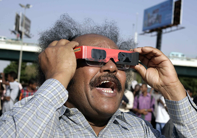 A Sudanese man reacts as he looks through tinted glasses towards the sun to watch a partial solar eclipse over the Sudanese capital Khartoum, on November 3, 2013. (AFP Photo / Ebrahim Hamid)