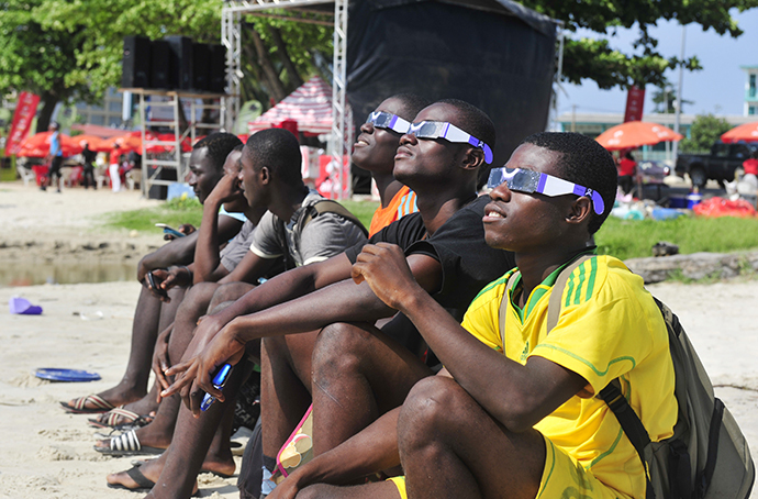 People look at a rare solar eclipse wearing special glasses, on November 3, 2013 in Libreville. (AFP Photo / Steve Jordan)