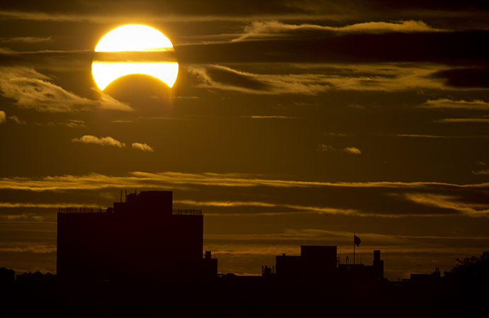 A partial Solar eclipse is seen just after sunrise over the Queens borough of New York across the East River on November 3, 2013 in New York. (AFP Photo / Stan Honda)