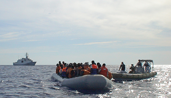 In this handout picture released by the Italian navy on October 31, 2013 migrants sit in a boat during a rescue operation off the coast of Sicily on October 30, 2013. (AFP Photo / Marina Militare)
