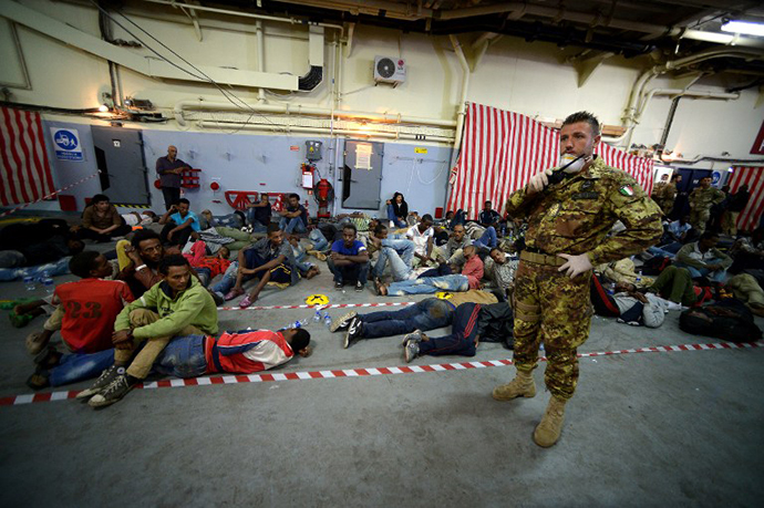 Some of the 219 migrants sit inside the Italian Navy amphibious assault ship San Marco after being rescued off the island of Lampedusa on October 25, 2013. (AFP Photo / Filippo Monteforte)
