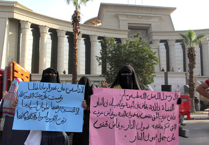 Veiled women supporters of the ousted Egyptian president Mohammed Morsi hold up signs with Islamic text written in Arabic, as they rally outside the High Court in Cairo, on November 4, 2013. (AFP Photo / Mohamed Kamel)