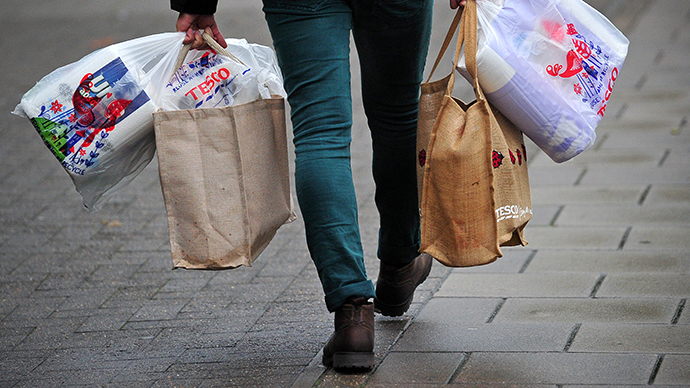 A man carries his shopping after visiting a Tesco store in south London (AFP Photo / Carl Court)