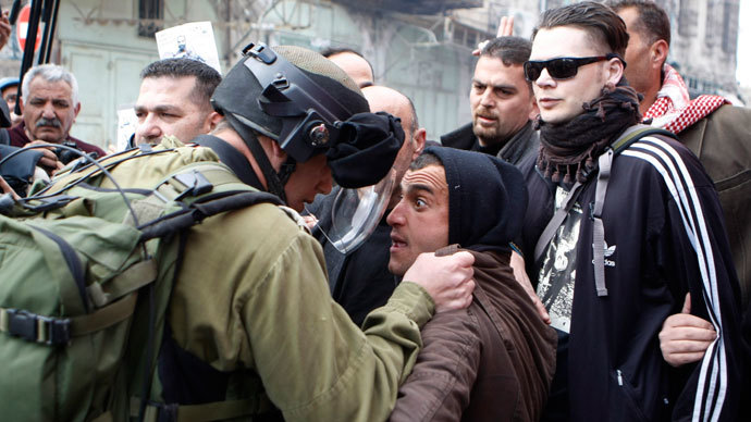 An Israeli soldier argues with a Palestinian protester during clashes in the West Bank city of Hebron March 1, 2013.(Reuters / Mussa Qawasma)