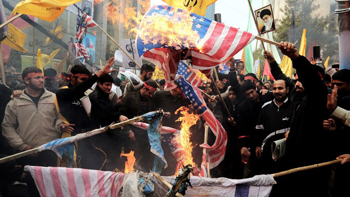 Iranians burn US flags outside the former US embassy in Tehran on November 4, 2013, during a demonstration to mark the 34th anniversary of the 1979 US embassy takeover. (AFP Photo)