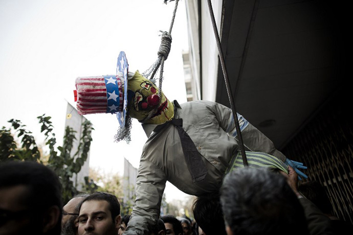 An Iranian man holds an effigy of Uncle Sam with a rope around his neck outside the former US embassy in Tehran on November 4, 2013, during a demonstration to mark the 34th anniversary of the 1979 US embassy takeover. (AFP Photo / Behrouz Mehri)
