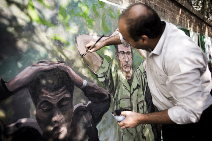 An Iranian man puts the final touches on his painting outside former US embassy in Tehran on November 4, 2013, depicting the US hostages after the seizing the US embassy in 1979, during a demonstration to mark the 34th anniversary of the 1979 US embassy takeover. (AFP Photo / Behrouz Mehri)