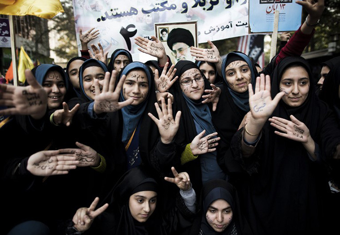 Iranian schoolgirls show their palms with anti-US slogans outside the former US diplomatic mission in Tehran during a demonstration on November 4, 2013 to mark the 34th anniversary of the 1979 US embassy takeover. (AFP Photo / Behrouz Mehri)
