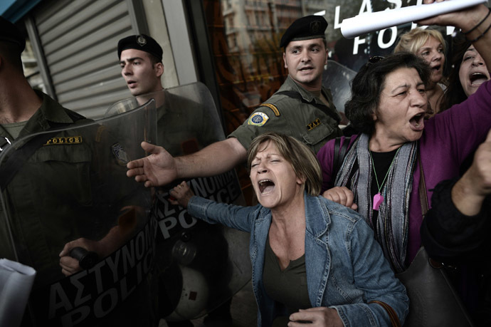 Protesters are pushed back from the riot police as EU and IMF officials escorted out from the emergency exit of the Greek Finance Ministry after their meeting with the Greek Finance Minister in Athens on November 5, 2013. (AFP Photo/Aris Messinis)