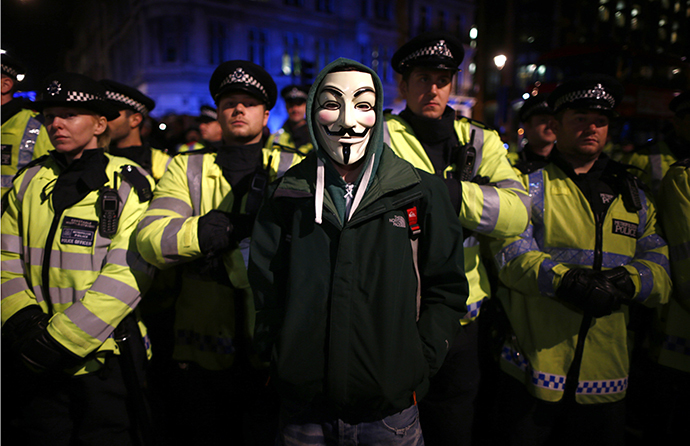 A protester wearing a Guy Fawkes mask stands in front of a line of riot police officers during a protest against budget cuts and energy prices in Westminster, central London, November 5, 2013. (Reuters / Andrew Winning)