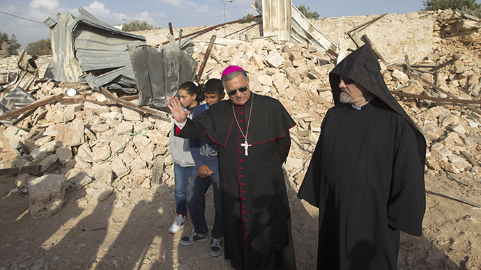Children look on as Latin Patriarch of Jerusalem Fouad Twal (C) stands amongst the ruins of a Palestinian home, on November 5, 2013. (AFP Photo / Ahmad Gharabli)