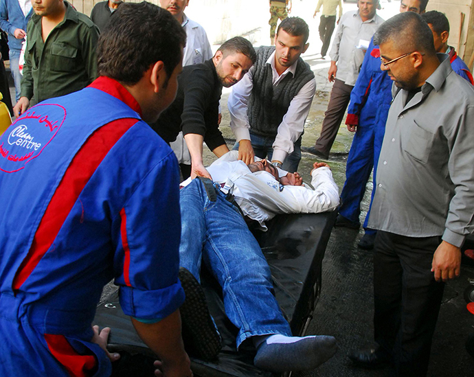 A handout picture released by the official Syrian Arab News Agency (SANA) on November 6, 2013, shows Syrians carrying an injured man after a bomb explosion allegedly rocked the heart of the Syrian capital Damascus. (AFP Photo)