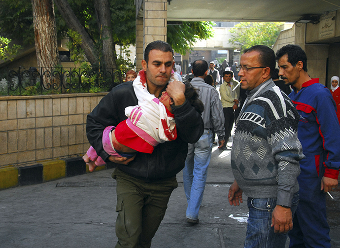 A man carries an injured child after a bomb explosion in front of the al-Hejaz train station in central Damascus November 6, 2013 in this picture provided by Syria's national news agency SANA. (AFP Photo)