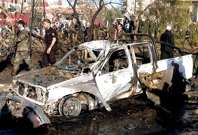 People gather around wreckage after a car bomb in Suweida city, November 6, 2013, in this handout picture released by Syria's national news agency SANA. (Reuters)