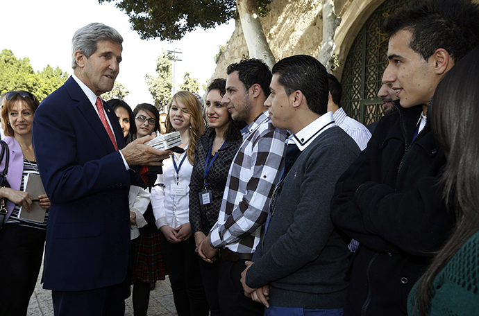 US Secretary of State John Kerry is offered a gift by young Palestinian people during a visit near Manger Square on November 6, 2013 in the West Bank city of Bethlehem. (AFP Photo / Jason Reed)