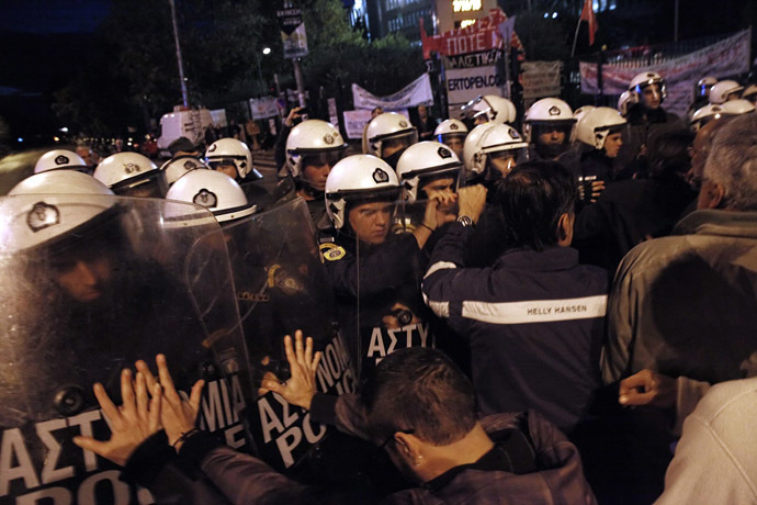 Riot police clash with people gathered outside the headquarters of former public broadcaster ERT in Athens on November 7, 2013. (AFP Photo/Kostis Ntantamis)