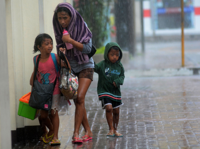 A mother and her children brave heavy rains as they head for an evacuation center amidst strong winds as Typhoon Haiyan pounded Cebu City, in central Philippines on November 8, 2013 (AFP Photo)