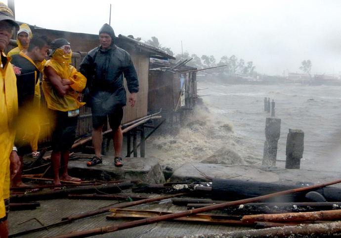 People stand at the pier as Super Typhoon Haiyan smashes into coastal communities on the central island of Bacalod on November 8, 2013. (AFP Photo / Julius Mariveles)