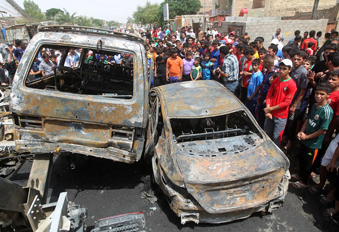 Iraqis gather around burnt vehicles at the site of a car bombing at a market in Baghdad's impoverished district of Sadr City on May 16, 2013 as at least eight people were killed in blasts across the country. (AFP Photo / Ahmad Al-Rubaye)