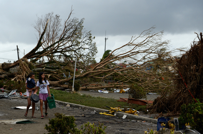 Women walk past fallen trees and destroyed houses in the aftermath of Super Typhoon Haiyan in Tacloban, eastern island of Leyte on November 9, 2013.(AFP Photo / Noel Celis)