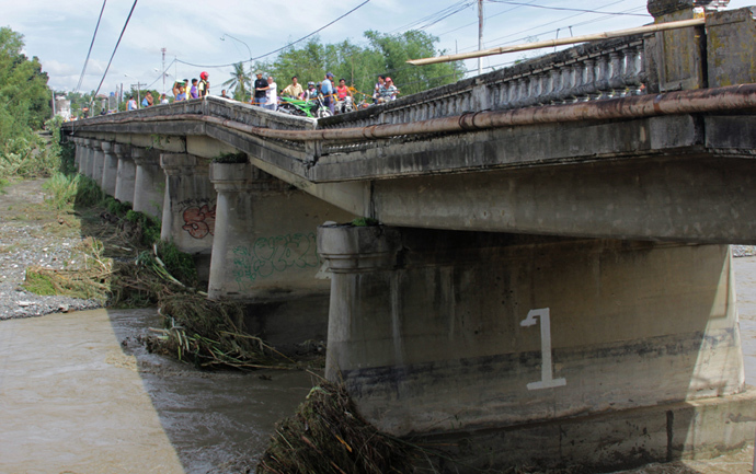 People look at a damaged bridge in the aftermath of Super Typhoon Haiyan in Iloilo on November 9, 2013. (AFP Photo / Tara Yap)