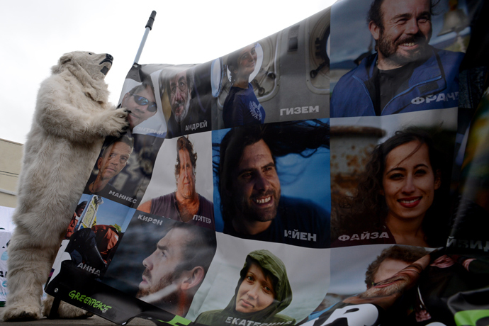 "Wearing costume of a polar bear a Greenpeace activist holds a poster with pictures of the ""Arctic 30"" detained Greenpeace activists during a rally in their support (AFP Photo)"