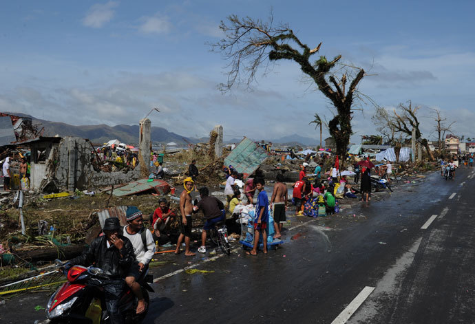 Residents take a bath and wash their belongings next to debris along a road in Tacloban, on the eastern island of Leyte on November 10, 2013 after Super Typhoon Haiyan swept over the Philippines.(AFP Photo / Ted Aljibe)