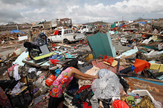 A woman dries her clothes near thousands of damaged houses after super Typhoon Haiyan battered Tacloban city, central Philippines November 10, 2013.(Reuters / Romeo Ranoco)