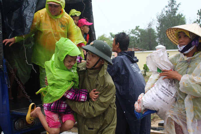 A soldier assists a young girl as villagers are evacuated to a safe place by a military truck in preparation for the arrival of the super typhoon Haiyan in the central province of Quang Nam on November 9, 2013.(AFP Photo / STR)